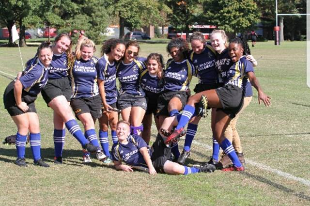 St. Mary's College women's rugby team poses for a picture on an outdoor football field