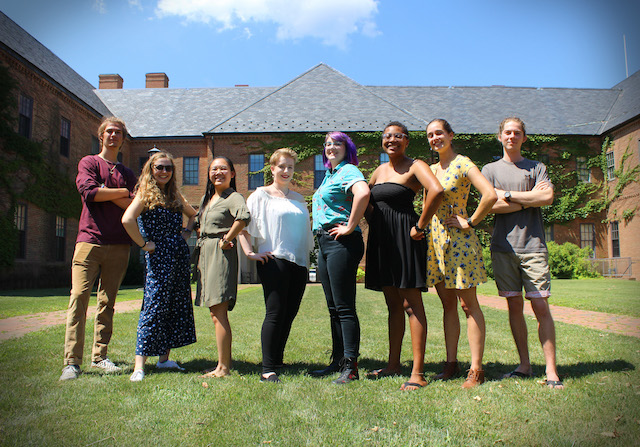 8 confident looking diverse students stand on the lawn in front of an academic building