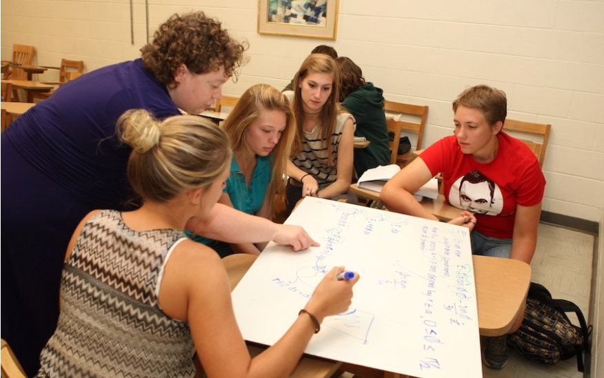 Physics professor Erin De Pree (standing) works with a group of students at St Mary's College of Maryland. Credit: Michelle Milne
