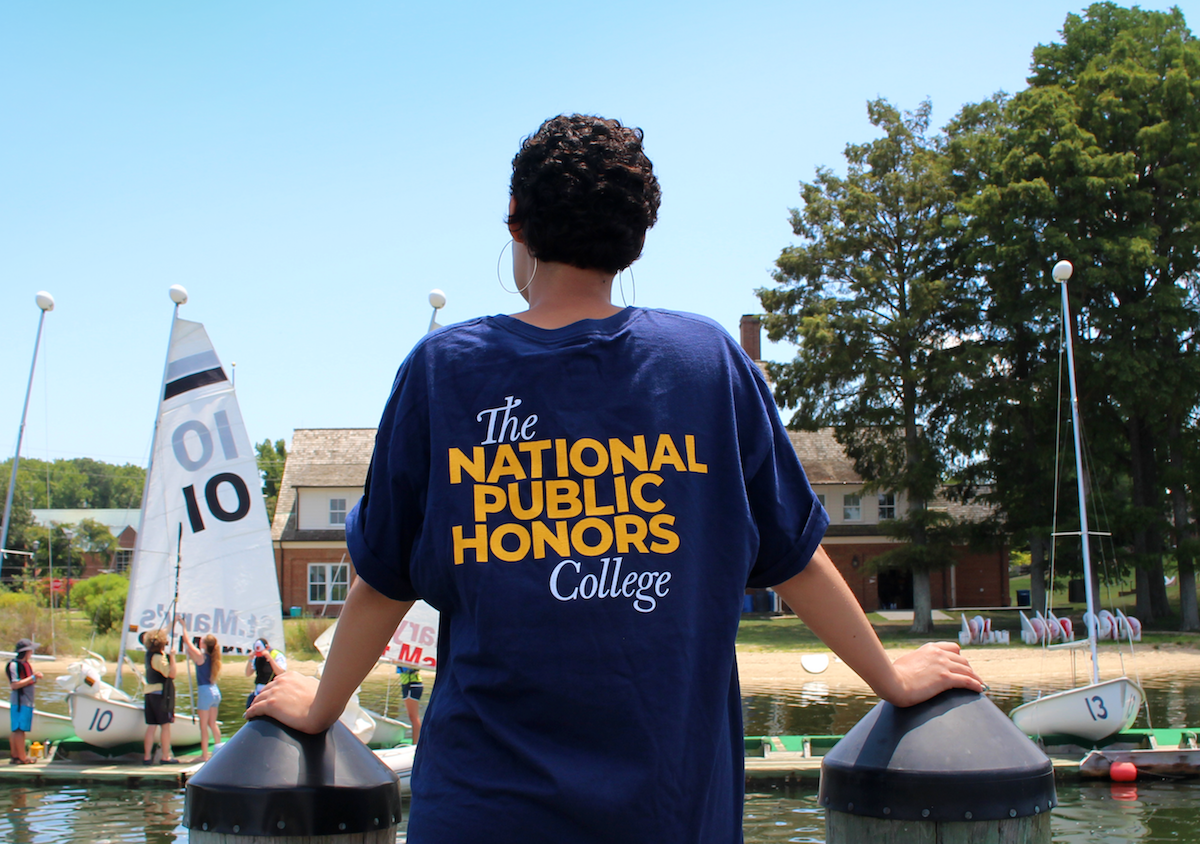 student facing riverfront with national public honors college tee shirt