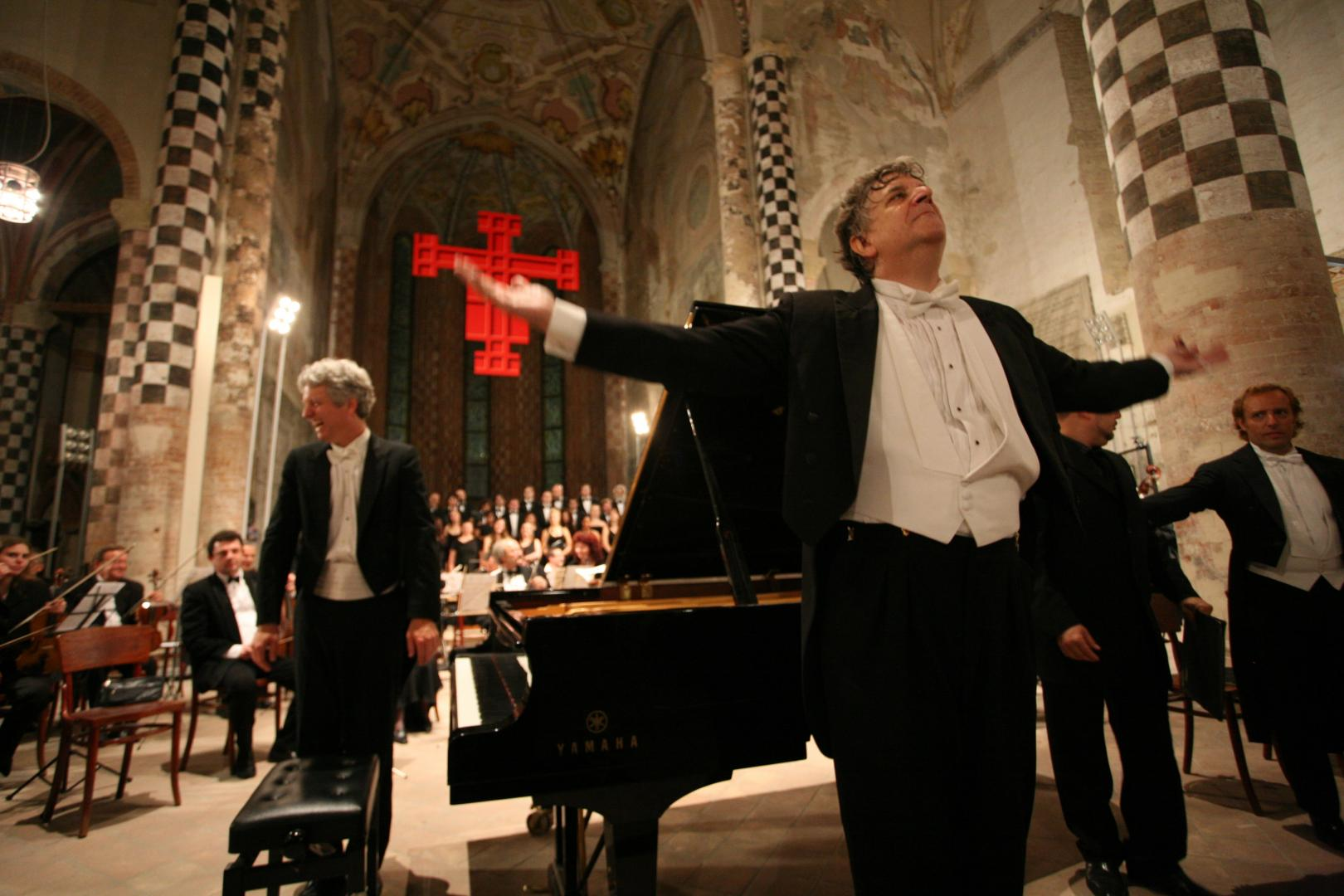 Pictured: A previous performance by Brian Ganz, left, at the Alba Music Festival in Alba, Italy, conducted by Larry Vote, center.