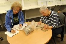 Isabel Tonkavitch and Sara Fisher cleaning and cataloging artifacts in the anthropology lab at St. Mary's College