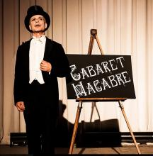 Cabaret Macabre image of conductor in front of sign board with name of the play