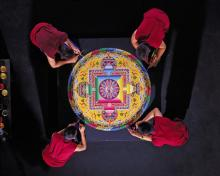 Tibetan Buddhist Monks constructing a Mandala Sand Painting shown
