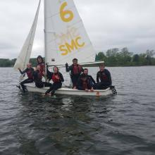 A sailing team smiles from a sailboat in the middle of the river