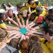 A coed frisbee team lays on the ground in a circle around a frisbee.