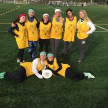 The women's ultimate frisbee team poses on a grassy field with a frisbee