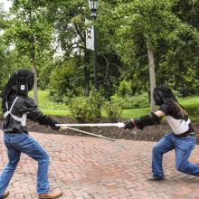 Two St. Mary's College students engaged in a fencing battle.